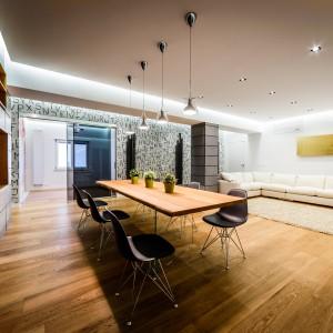 Jadalnię połączono z salonem. Przestrzeń wypoczynku wyznacza miękki, jasny dywan i bardzo duży, mięsisty narożnik w harmonizującym z dywanem kolorze. Projekt i zdjęcia: Marco Marotto, Paola Oliva, Brain Factory.
