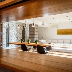 Otwór wydrążony w elemencie działowym otwiera widok na salon i jadalnię z poziomu kuchni. Może także pełni rolę blatu stołowego. Projekt i zdjęcia: Marco Marotto, Paola Oliva, Brain Factory.