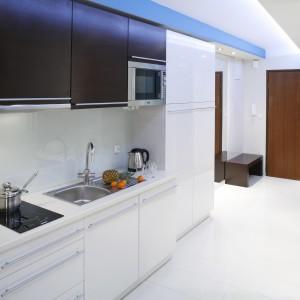 W kuchni dominuje biel, wykończona na wysoki połysk. Dzięki doborze kolorów i faktur, meble odbijają światło i rozświetlają wnętrze. Wtóruje im biała ściana nad blatem zabezpieczona szkłem. Projekt: Agnieszka Burzykowska-Wałkosz. Fot. Bartosz Jarosz.