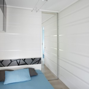 Za wąskim pasem lustra ukryta została pojemna szafa. Dodatkowo lustro powiększa dość wąską i małą sypialnię. Projekt: Marta Kilan. Fot. Bartosz Jarosz.