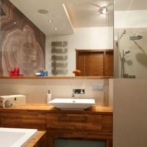 Drewno odgrywa bardzo istotną rolę w aranżacji tej łazienki. Doskonale łączy się z naturalnym kamieniem na ścianie oraz białą ceramiką. Projekt: Kuba Kasprzak, Paweł Pałkus.