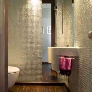 Do toalety dla gości wybrano szklaną mozaikę  w kolorze srebrnym, która zdobi wszystkie ściany. Od powierzchni mozaiki pięknie obija się światło i rozświetla całe wnętrze. Projekt: Małgorzata Szajbel-Żukowska. Fot. Bartosz Jarosz.
