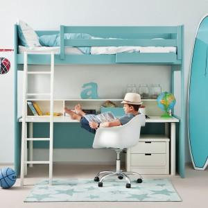 Nowoczesne łóżko na antresoli wprowadza do wnętrza iście wakacyjny klimat. Aranżację uzupełnia białe krzesło obrotowe oraz seledynowy dywan w gwiazdki. Fot. Cuckooland.