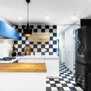 Jedną ze ścian w przestrzeni dziennej pomalowano na kolor głębokiej czerni. Koresponduje ona z szachownicą na podłodze i ścianie nad blatem, ciemną kanapą w salonie, a także stanowi tło dla czarnej, wolno stojącej lodówki, która zdaje się wtapiać w powierzchnię za nią. Był to celowy zabieg, dzięki którego sprzęt AGD nie zaburza porządku wizualnego w kuchni. Projekt: COCO Pracownia projektowania wnętrz. Fot. Łukasz Markowicz.