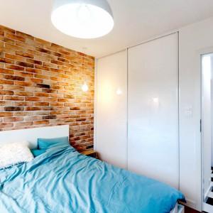 Cegła na ścianie za łóżkiem buduje w sypialni ciepłą atmosferę. Z kolei połyskujące fronty garderoby, odbijając światło, optycznie powiększają wnętrze. Projekt: COCO Pracownia projektowania wnętrz. Fot. Łukasz Markowicz.