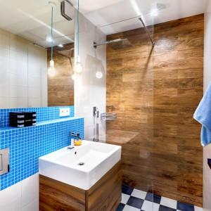 W łazience spotykają się barwy i faktury obecne w innych pomieszczeniach mieszkania. Podłogę pokrywa posadzka-szachownica, ścianę w strefie prysznica wykończono drewnopodobnymi płytkami, korespondującymi z drewnem w sypialni i salonie, a ściana nad wc i umywalką pokryta została błękitną mozaiką, w kolorze korespondującym z barwą górnych szafek w kuchni i jadalni. Błękitne są również kable, na których wiszą edisonowskie żarówki. Projekt: COCO Pracownia projektowania wnętrz. Fot. Łukasz Markowicz.