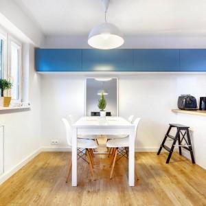 """Po wyburzeniu ściany działowej, oddzielającej kuchnię od salonu z jadalnią i po """"wprowadzeniu"""" do kuchni półwyspu, przestrzeń pomiędzy nim a oknem, wykorzystano na urządzenie miejsca do spożywania posiłków. Tutaj także, podejmowaniu są goście, a półwysep sprzyja interakcji podczas domowych imprez. Projekt: COCO Pracownia projektowania wnętrz. Fot. Łukasz Markowicz."""