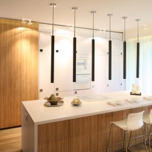 Zabudowa kuchenna pokrywa całą ścianę w tej kuchni. Śnieżną biel, w którą wpasowano równie biały sprzęt AGD, zestawiono z frontami w kolorze ciepłego, jasnego drewna. Całość prezentuje się zarówno nowocześnie, jak i przytulnie. Projekt: Dominik Respondek. Fot. Bartosz Jarosz.