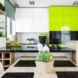 Mocnym akcentem aranżacji tej kuchni jest soczysta limonkowa zieleń wysokiej zabudowy, wybijająca się ze stonowanego tła w kolorach bieli i ciepłego, jasnego drewna dębowego. Projekt: Małgorzata Błaszczak. Fot. Pracownia Mebli Vigo.
