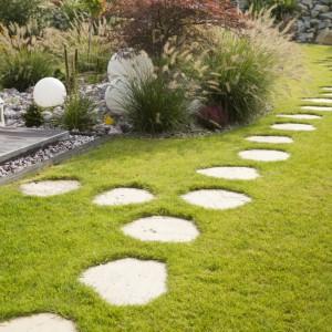 Płyty deptakowe stanowią ciekawą alternatywę dla tradycyjnych ścieżek ogrodowych. Wykonane z pojedynczych, nieregularnych elementów dodają przestrzeni ogrodowej charakteru. Płytki dostępne są w ofercie firmy Bruk-Bet. Fot. Bruk-Bet.