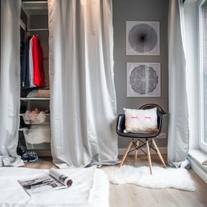 Kosmaty dywan i liczne tekstylia ocieplają wnętrze sypialni. Za zasłoną schowano praktyczną garderobę, na którą miejsce wygospodarowano we wnęce w ścianie. Projekt: Raca Architekci. Fot. Adam Ościłowski.