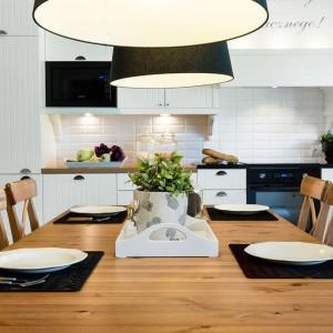 Drewniany stół z wygodnymi krzesłami dodaje białej kuchni ciepłego klimatu. Projekt: Małgorzata Błaszczak, Pracownia Mebli Vigo. Fot. Artur Krupa.