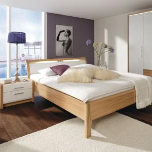 Nowoczesny zestaw La Vida niemieckiej marki Nolte Delbruck tworzy łóżko z wywiniętym zagłówkiem, dwa stoliki nocne oraz czterodrzwiowa szafa z praktycznymi szufladami. Wszystkie meble wykonane są z jasnego orzecha oraz ozdobione elementami z białego MDF-u. Fot. In House.