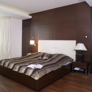Zabudowa na całą ścianę, w kolorze czekoladowego brązu nie tylko pełni funkcję praktyczną. Podkreśla też elegancki wygląd przestronnej sypialni. Projekt: Ewelina Janowska. Fot. Monika Filipiuk-Obałek.