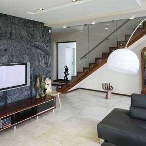 Telewizor w salonie powieszona na ścianie wyłożonej eleganckim kamieniem w czarno-szarej tonacji kolorystycznej. Projekt: Piotr Stanisz. Fot. Bartosz Jarosz.