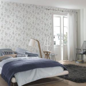 Jasnoszare kwiaty zdobiące białą tapetę z kolekcji Tendresse marki Rash dodadzą lekkości każdej sypialni, kreując wyciszający wygląd pomieszczenia. Fot. Rash.