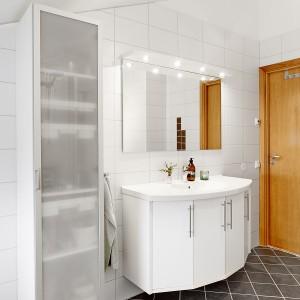 Do łazienki pod skosami prowadzą drewniane, dębowe drzwi. Wprowadzają one cieplejszy element do chłodnej aranżacji pomieszczenia. Fot. Vastanhem.