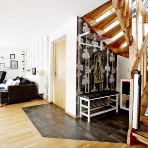 Do domu prowadzą drewniane, solidne drzwi. Wokół strefy wejścia podłogę wyłożono płytkami ceramicznymi, łatwymi w utrzymaniu w czystości. Miejsce na okrycia wierzchnie zaznaczono ciemną tapetą z białym wzorem. Fot. Vastanhem.