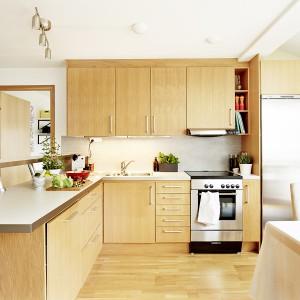 Kuchnia urządzona jest w ciepłych kolorach drewna. Meble idealnie harmonizują z drewnianą podłogą. Całość przełamano delikatnymi szarościami w postaci jasnego blatu i dużej, stalowej lodówki w obudowie. Fot. Vastanhem.