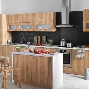 Meble z pionowym dekorem drewna w jasnym, przytulnym kolorze. Fronty są delikatnie zdobione, ale brak oczywistych uchwytów nadaje im nowoczesny charakter. Klasycyzujący dotyk wprowadzają przeszklenia w górnych szafkach. Fot. Castorama, kuchnia Stella.