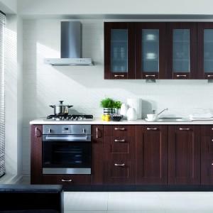 Jednorzędowa zabudowa w klasycznym stylu została utrzymana w wiśniowym odcieniu drewna malaga. Zdobne fronty są dodatkowo udekorowane metalowymi, dużymi uchwytami. Górne szafki urozmaicają delikatnie mleczne przeszklenia. Fot. Black Red white, seria Family Line, kuchnia Edan.
