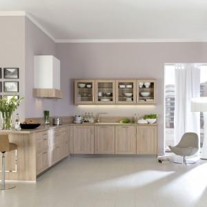 Piękna, klasycyzująca kuchnia w kolorze jasnego drewna. Fronty dolnej zabudowy są delikatnie zdobione, a szafki górne przeszklono, pozwalając na wyeksponowanie zastawy stołowej. Fot. Brigitte.
