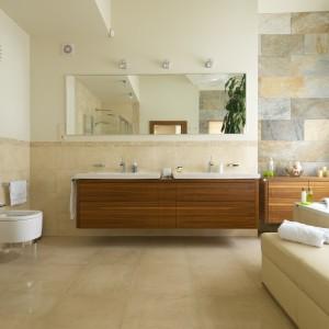 W przestronnej łazience jasne odcienie łączą się z geometryczną formą ceramiki oraz naturalnymi materiałami. Podwieszana szafka razem z prostokątnym lustrem wizualnie wyznacza strefę umywalkową. Projekt: Tomasz Tubisz. Fot. Przemysław Andruk.