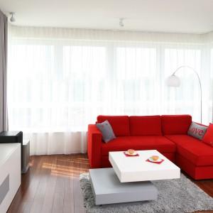 W urządzanym w zgodzie założeniami minimalizmu salonie dominują biele i szarości. Czerwony kolor narożnika zastępuje tu wszelkie inne dekoracje. Ustawiony przy oknie pozwolił w pełni zagospodarować przestrzeń niewielkiego mieszkania. Projekt: Iza Szewc. Fot. Bartosz Jarosz.