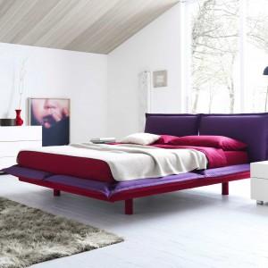 Przestrzeń sypialni zdominowanej bielą ciekawie ożywia efektowne łóżko łączące barwy burgunda i fioletu. Fot. Roche Bobois.
