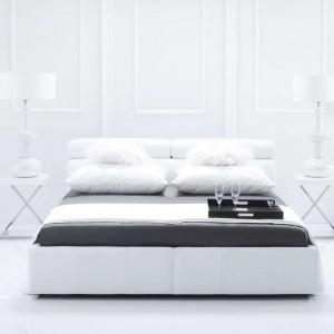 Nowoczesne łóżko tapicerowane białą skórą zestawiono z wysokimi komodami o falistej, lekko romantycznej formie. W połączeniu z eleganckimi stolikami powstała aranżacja piękna, a zarazem uniwersalna. Fot. Kler.