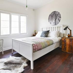 Białą sypialnię dobrze jest urządzić we wnętrzu z podłogą w kolorze ciemnego drewna. Nada ona aranżacji wyrazisty charakter oraz ociepli wnętrze. Fot. Cranmore Home.