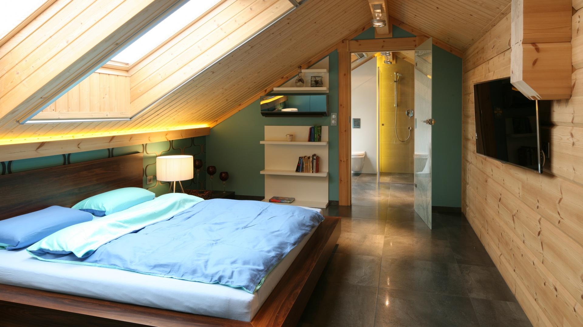 Strefa poddasza została podzielona na sypialnie i sąsiadującą z nią łazienkę. Obie przestrzenie łączy podobna stylistyka, kolor i materiały. Projekt: Tomasz Motylewski,  Marek Bernatowicz. Fot. Bartosz Jarosz.