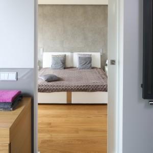 Wystarczy otworzyć przesuwane drzwi z transparentnego szkła, a by przejść z sypialni do łazienki. Oba pomieszczenia urządzone są w podobnej stylistyce. Projekt: Małgorzata Galewska. Fot. Bartosz Jarosz.