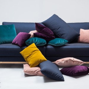 Sofa Presto powstała dla marki Comforty. Linia oparcia płynnie przechodząca w podstawę, wraz z poduchami, tworzą harmonijny układ brył. Całość unosi się na charakterystycznych nóżkach – drewnianych lub stalowych. Fot. Comforty.