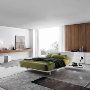 Dla zrównoważenia chłodnej bieli warto wykorzystać w sypialni elementy w kolorze drewna. Ściana wyłożona panelami czy prosta, drewniana półka nada wnętrzu zupełnie inny wygląd. Fot. Presotto.