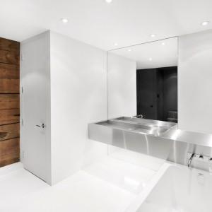 Ultranowoczesna łazienka ze stalową umywalką, w blat której zamontowano również baterię wannową. Chłodną, minimalistyczną aranżację ociepla drewniany motyw na ścianie przy drzwiach. Projekt: Anne Sophie Goneau. Fot. Adrien Williams.
