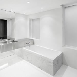 Minimalizm panujący w łazience delikatnie przełamuje obudowa wanny z marmurowym dekorem. Projekt: Anne Sophie Goneau. Fot. Adrien Williams.