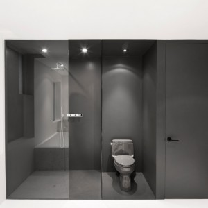 Strefę prysznica i wc umieszczono w oryginalnym czarnym kubiku, schowane za czarnym przeszkleniem. Wypełniona czernią przestrzeń w efektowny sposób kontrastuje z otaczającą go bielą. Projekt: Anne Sophie Goneau. Fot. Adrien Williams.