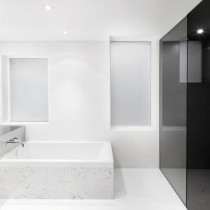 W łazience symetria ściera się z asymetrią. Z porządku dużych, prostokątnych powierzchni wyłamuje się stalowy blat umywalki, nachodzący na wannę w asymetrycznej manierze. Projekt: Anne Sophie Goneau. Fot. Adrien Williams.