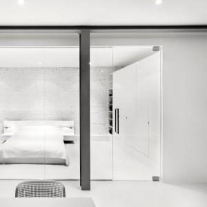 Za przeszkloną, przeźroczystą ścianą, równoległą do jadalni urządzono przestronną, jasną master bedroom. Projekt: Anne Sophie Goneau. Fot. Adrien Williams.
