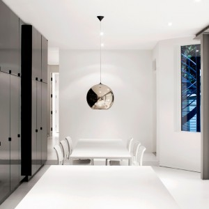 Z bielą i jasną szarością efektownie kontrastuje czerń zabudowy meblowej. Wykończenie na wysoki połysk sprawia, iż mimo ciemnego koloru, fronty nadają przestrzeni lekki charakter i powiększają ją optycznie. Projekt: Anne Sophie Goneau. Fot. Adrien Williams.