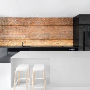 Z czarną zabudową kuchenną wykończoną w połysku kontrastuje biała, matowa wyspa, która pełni także funkcję dwuosobowego barku śniadaniowego. Projekt: Anne Sophie Goneau. Fot. Adrien Williams.