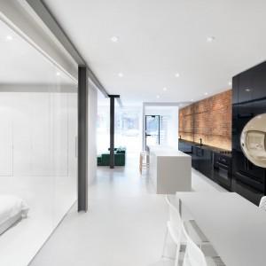 Matowa powierzchnia cegły w kuchni kontrastuje z połyskującymi frontami długiej zabudowy. Połysk widoczny jest również w postaci dekoracyjnej lampy nad stołem jadalnianym, a także na podłodze, znajdującej się za transparentną ścianą sypialni. Projekt: Anne Sophie Goneau. Fot. Adrien Williams.