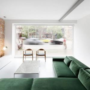 Kolorowym akcentem w salonie jest miękki narożnik o barwie butelkowej zieleni. Siedząc na nim można oglądać telewizję lub widoki za panoramicznym oknem. Projekt: Anne Sophie Goneau. Fot. Adrien Williams.
