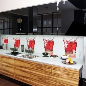 Górna zabudowa w połyskującej czerni idealnie komponuje się z kolorowymi drinkami, zdobiącymi ścianę nad blatem. Razem tworzą typowo męską aranżację kuchni. Fot. Redro.