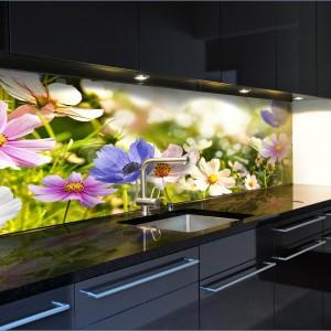 Kuchnię, w której dominuje czerń ożywiono fototapetę w kolorach wiosny. Kwiecista łąka z kolorowymi kwiatami ożywia i rozwesela nieco smutną aranżację kuchni w ciemnych kolorach. Fot. Grafdeco.