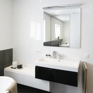 W minimalistycznie urządzonej łazience nad prostokątnym lustrem umieszczono oprawę o prostej formie. Projekt: Beata Kruszyńska. Fot. Bartosz Jarosz.