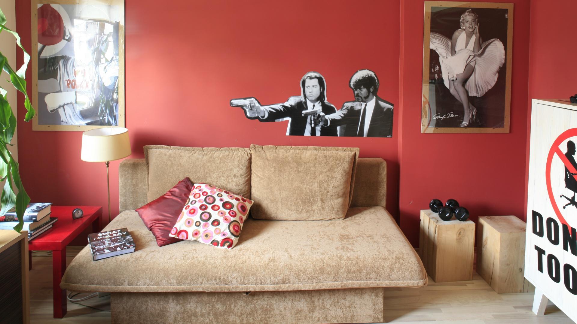 Rolę tradycyjnego łóżka pełni niewielka sofa z funkcją spania. W ciągu dnia jest ona wygodnym siedziskiem dla odwiedzających chłopca kolegów, natomiast nocą zapewnia wygodny odpoczynek. Strefę gościnną uzupełnia niewielki czerwony stolik. Fot. Bartosz Jarosz.