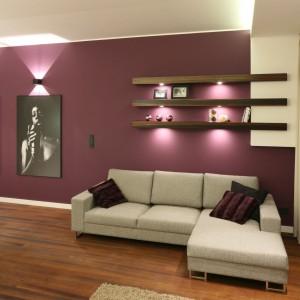 Połączony z kuchnią salon urządzono w neutralnych beżach i brązach. Wyeksponowano jedynie ścianę za kanapą - w głębokim fioletowym kolorze stanowi ciekawe tło dla czarno-białych dekoracji. Projekt: Katarzyna Mikulska-Sękalska. Fot. Bartosz Jarosz.