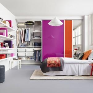 Aby ożywić sypialnię wystarczy wprowadzić do jej wystroju kilka barwnych elementów. Ciekawym rozwiązaniem będzie np. garderoba z przesuwnymi drzwiami w neonowym odcieniu różu i pomarańczu. Dla wzmocnienia efektu warto zastosować też kilka drobnych dodatków w tych samych kolorach. Fot. Elfa.